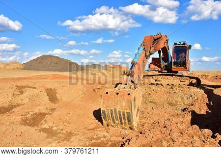 Excavator Working On Earthmoving At Open Pit Mining On Blue Sky Background. Backhoe Digs Sand In Qua