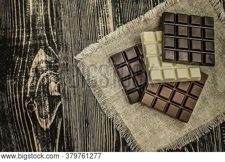 Dark , Milk And White Chocolate Bar. Chocolate Over Rustic Wooden Background.