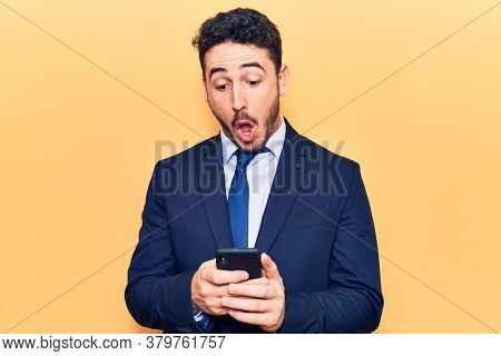 Young hispanic man wearing suit using smartphone scared and amazed with open mouth for surprise, disbelief face