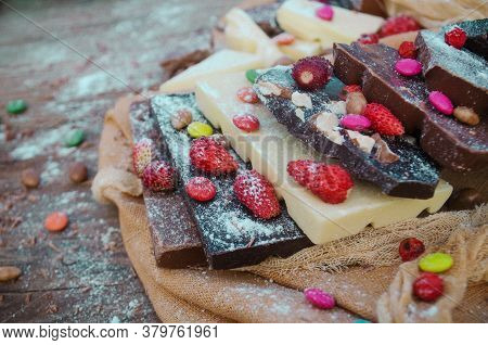 Chocolate Mix With Nuts And Dried Fruits On Rustic Wooden Background
