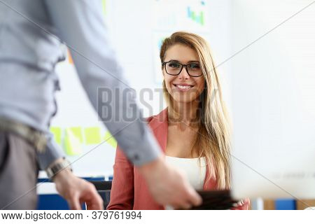 The Woman Sits In Front Of The Monitor In The Office And Smiles. Male Boss Has A Flexible Approach T
