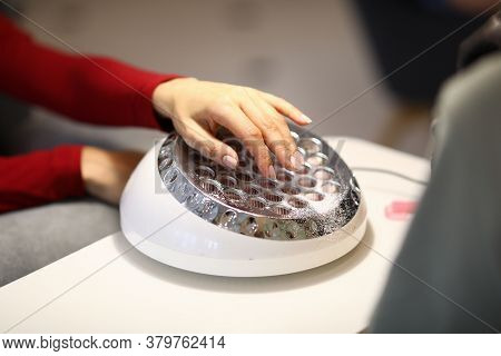 Female Hands Lie On The Lamp For Drying Manicure. Hands And Nails Look Well-groomed