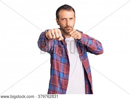 Young handsome man wearing casual clothes punching fist to fight, aggressive and angry attack, threat and violence