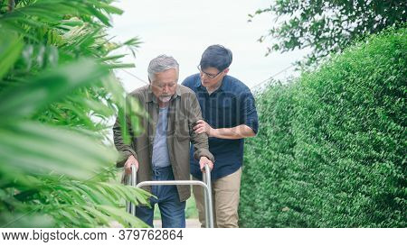 Son Helping Carer Old Father With Walking In Path Way At Home Garden For Relaxant Or Rehabilitation