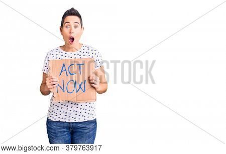 Young woman with short hair holding act now banner scared and amazed with open mouth for surprise, disbelief face