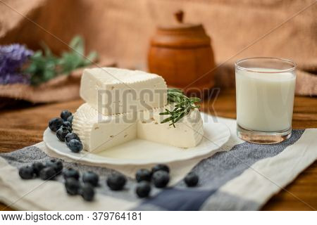 A Glass Of Goat Milk And A Head Of Goat Milk Cheese Stand On A Wooden Table. Cheese At Home.