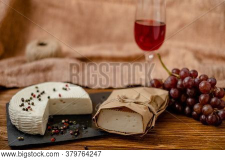 Goat Cheese, Grapes And Wine Lie On A Wooden Table. Cheese At Home.