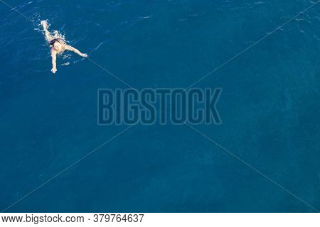 Aerial Top View Happy Young Woman In Black Swimsuit Swims In The Red Sea, Egypt, Sharm El Sheikh. Va