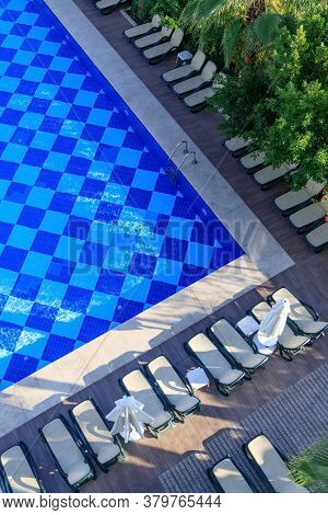 Top View Of The Pool, Sun Loungers And Umbrellas Among Lush Green Palms And Bushes In A Resort Hotel