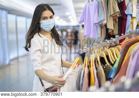 Woman With Face Mask Is Shopping Clothes In Shopping Center Woman With Face Mask Is Shopping Clothes