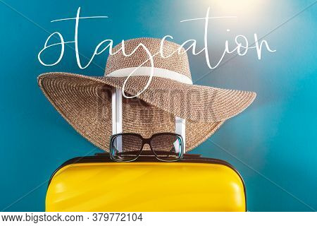 Staycation Word. Bright And Stylish Cabin Size Suitcase With Straw Hat Against Bright Blue Backgroun
