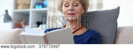 Grandmother Sits At Home And Read With Enthusiasm. Self-isolation Book An Elderly Woman At Home. An