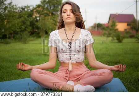 Young Beautiful Woman With Long Dreadlocks And Beads Made By Natural Stones Is Doing Meditation And