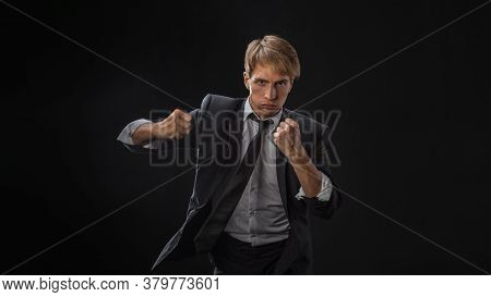 Competition In Business, Concept. A Young Man In A Suit And Tie Fights With His Fists, An Aggressive