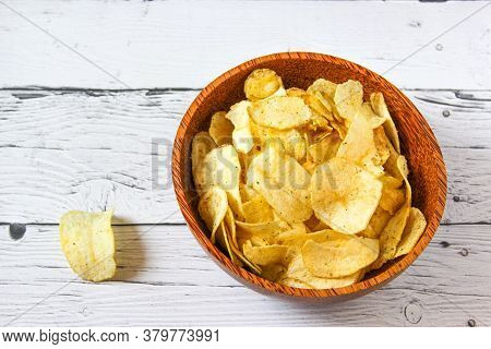 Potato Chips Or Crisps In Wooden Bowl Against White Wooden Background. Pile Of Potato Chips. Potato