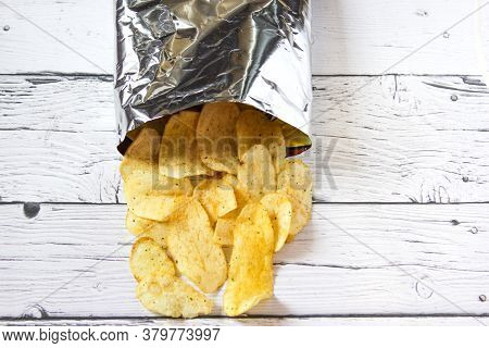 Food Concept With Potato Crisps In Bag On Wooden Background. Potato Chips And Pack. Packaging Of Chi