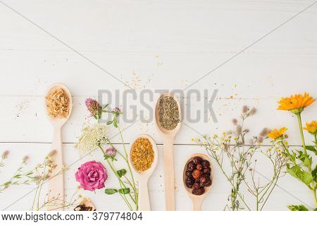 Top View Of Herbs In Spoons And Flowers On White Wooden Background, Naturopathy Concept