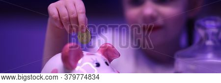 Little Girl Puts Coin In Piggy Bank On Table. Teach Child How To Save Money. Financial Literacy. Eff