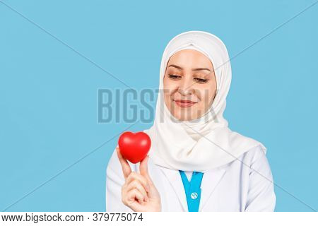 Portrait Of A Friendly, Muslim Woman Doctor Or Nurse With A Stethoscope And A Red Heart In Her Hand.
