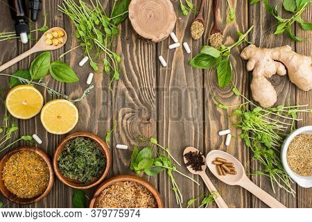 Top View Of Pills And Green Herbs On Wooden Surface, Naturopathy Concept