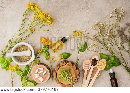 Top View Of Herbs, Green Leaves, Mortar With Pestle, Bottles And Pills In Wooden Spoons On Concrete