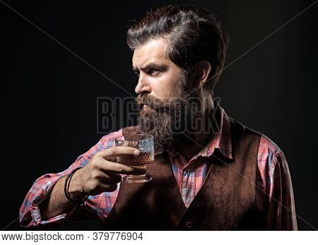 Man Holds Glass Of Brandy. Luxury Alcohol Drink. Cheerful Bearded Man Is Drinking Expensive Whisky O