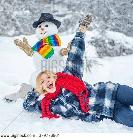 Snowman And Funny Girl In Winter Outside. Cute Snowman At A Snowy Village