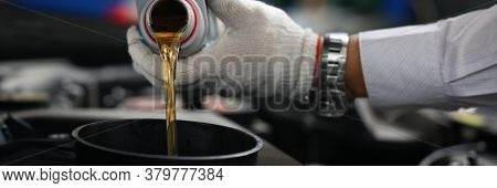 Close-up Hands In Gloves Pour Oil Into Car Tank. Selection Engine Oil. Necessary Volume Of Filling.