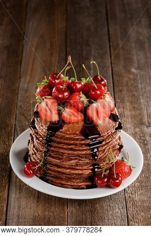 Pile Of Pancakes With Berries And Chocolate Pairing, On Wooden Background
