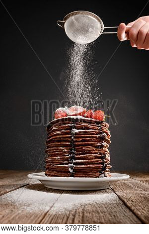 Hand Sprinkles Icing Sugar Onto A Pile Of Pancakes