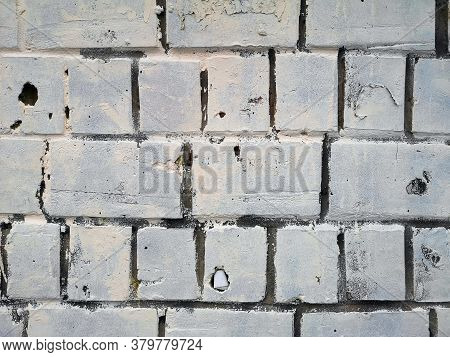 Old Brick Wall With Remains Of Paint. Background Texture Closeup.