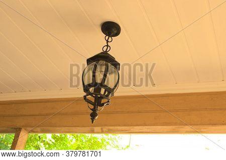 A Street Lamp Hangs On The Ceiling Of The Veranda. Suspended Metal Lamp, Black. The Lamp Is Screwed