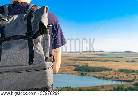 Close-up Backpack At Back Of Men Traveler Looking At The Horizon Under A Blue Sky. Rear View. Travel