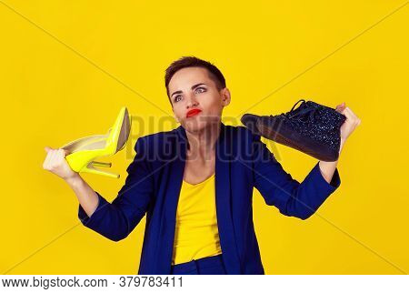 I Don't Know Which Pair To Choose Or Wear. Woman Holding One Pair Of High Heels And One Flat Shoes W