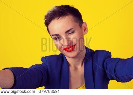 Winking, Selfie Shot. Closeup Woman Short Hair Girl Boy Alike Smiling Blinking Eye While Doing A Sel