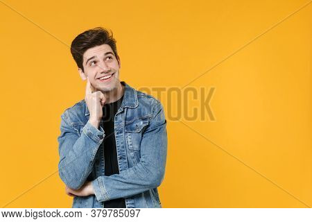 Pensive Young Man Guy In Casual Denim Jacket Posing Isolated On Yellow Background Studio Portrait. P
