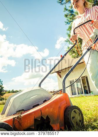 Gardening, Taking Care Of House Backyard, Agricultural Concept. Female Person Mowing Green Lawn With