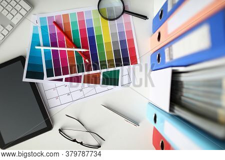 Close-up Of Color Palettes On Desk, Office Of Interior Design Studio. Files And Tablet, Pencils And