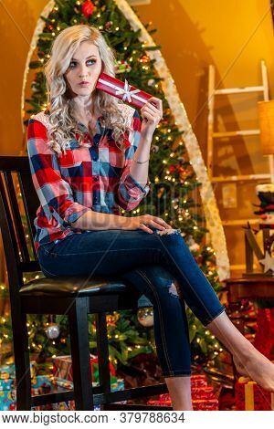 A gorgeous blonde model enjoys the holiday season at home with a Christmas tree and presents