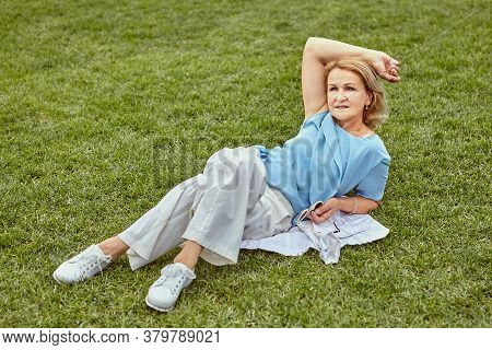 Senior Attractive Caucasian Woman About 60 Years Old In Casual Elegant Cloth Is Lying Down The Grass