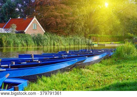 Landscape With Blue Wooden Boats On The River. A Row Of Boats By The River In The Morning. Blue Wood
