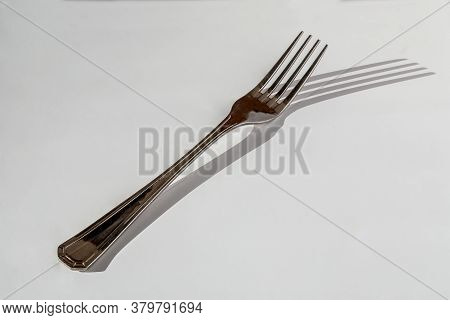 Elegant Stainless Fork On White Table With Sharp Sunny Shadow.