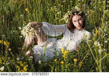 A Beautiful Woman In A White Dress In The Boho Style With A Wreath On Her Head Lies In A Field In Fl
