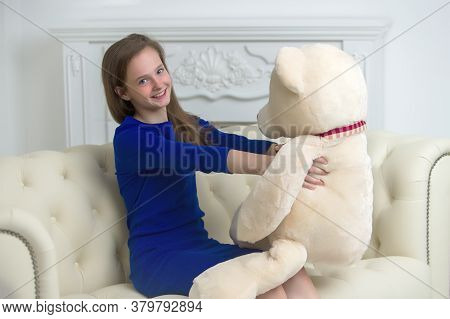 A Teenage Girl Of School Age Is Sitting On The Couch With A Big Teddy Bear. The Concept Of A Happy C