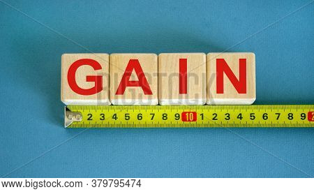 'gain' Word On Cubes Arranged Behind The Ruler On Beautiful Blue Background. Business Concept.