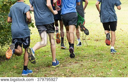 Rear View Of A Group Of High School Boys Training For Cross Country Running Grass In A Local Park.