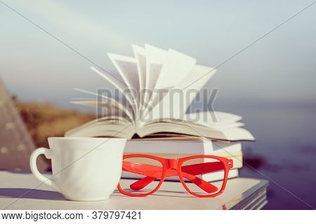 Reading On Holidays. Coffee Cup And Books On Table Outdoors Against Blue Sea Water Background. Book