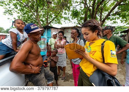 San Cristobal / Dominican Republic - May 16 2018: Brown Woman Signs Some Papers In Front Of A Shirtl
