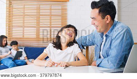 Asian Parents Homeschooling Their Children At Home. Father Teach Daughter Using Laptop Computer, Mot