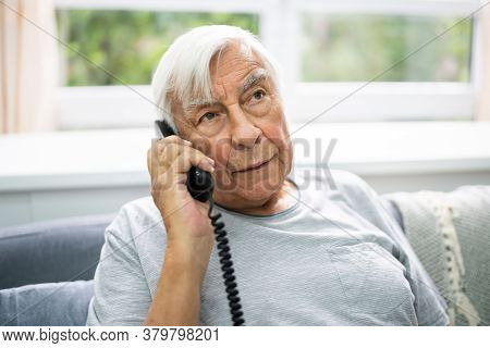 Senior Old Man Talking On Landline Telephone